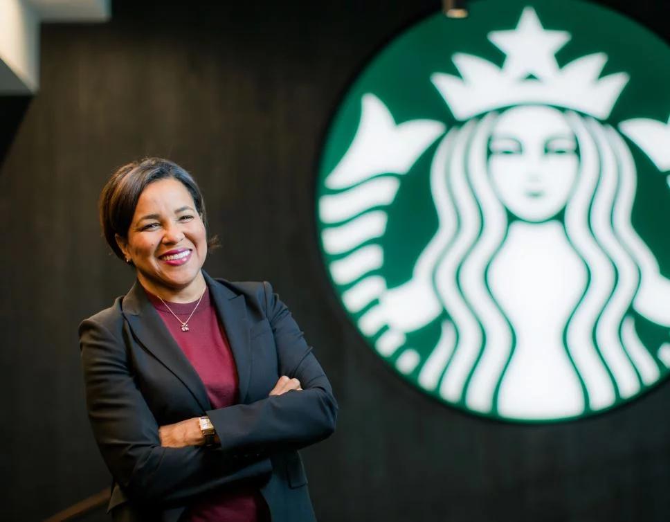 women next to Starbucks logo