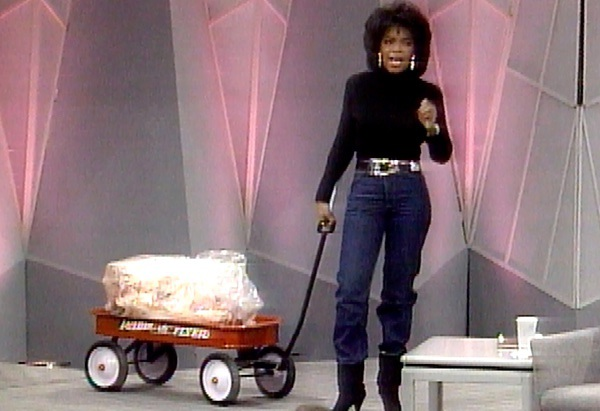 Oprah on her show in 1988, pulling a wagon full of fat