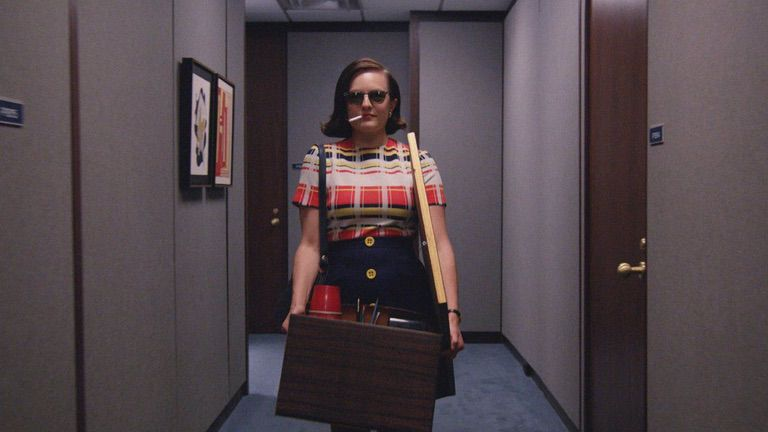 Peggy Olson walks down a hallway wearing sunglasses and smoking a cigarette