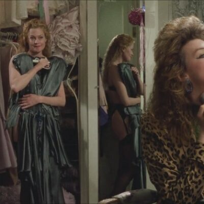 Melanie Griffith tries on clothes in front of a mirror, in the movie Working Girl