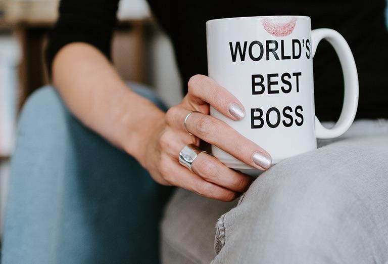 A woman's hand holds a mug reading WORLD'S BEST BOSS